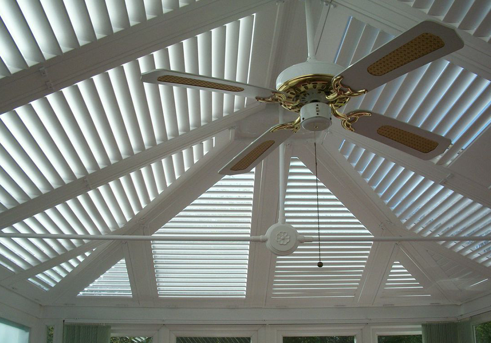 Modern custom shaped shutters in a conservatory